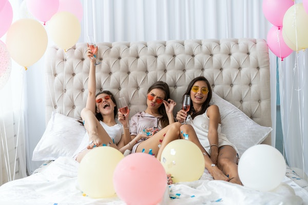 Pajama party. Attractive young smiling women in pajamas drinking champagne while having a slumber party in the bedroom