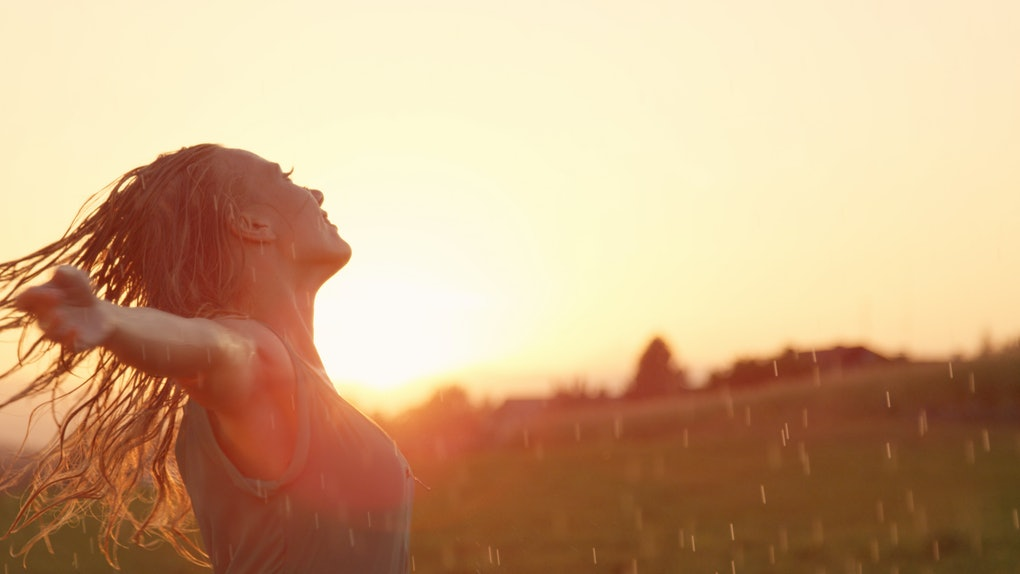 CLOSE UP, LENS FLARE, COPY SPACE: Smiling young woman spins in the rain with her arms outstretched. Blonde haired Caucasian girl playfully dances at stunning sunset. Female dancer improvising in rain