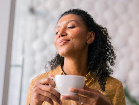 Feeling joyful. Curly dark-haired appealing woman wearing yellow blouse feeling joyful while drinking coffee