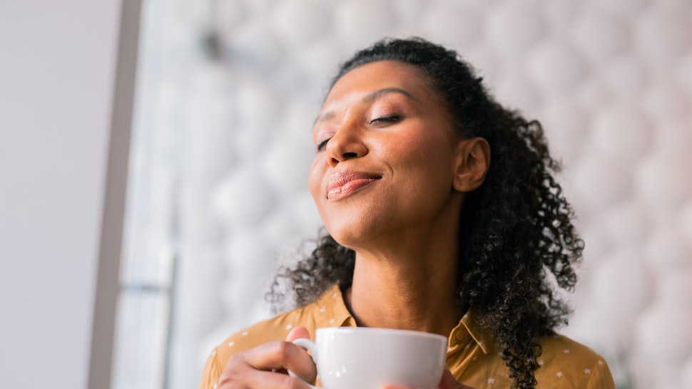 Feeling joyful. Curly dark-haired appealing woman wearing yellow blouse feeling joyful while drinking coffee