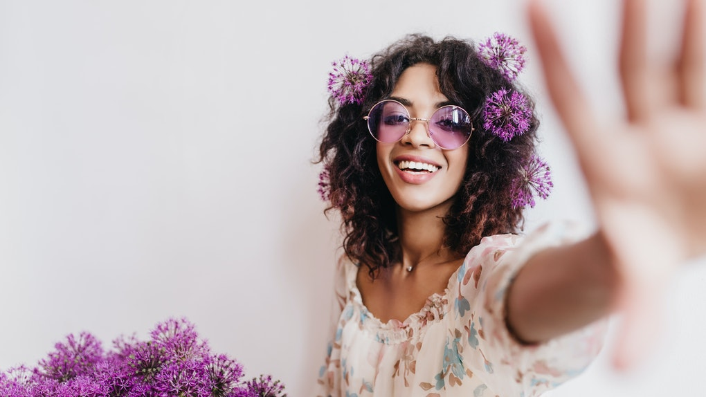 Attractive african girl having fun during photoshoot with flowers at home. Indoor portrait of dreamy black female model in purple sunglasses.