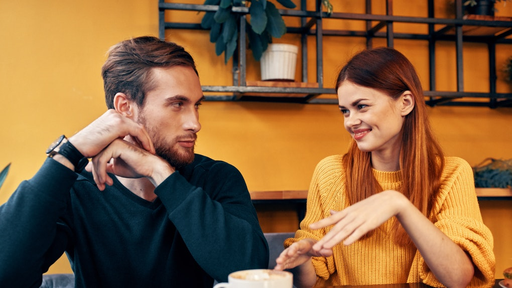 A woman in a yellow sweater man at a table in a cafe