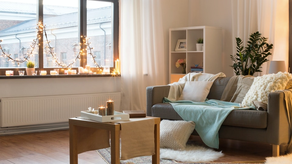 interior, christmas and interior concept - cushioned sofa, coffee table, garland string and candles on window sill in living room of cozy home
