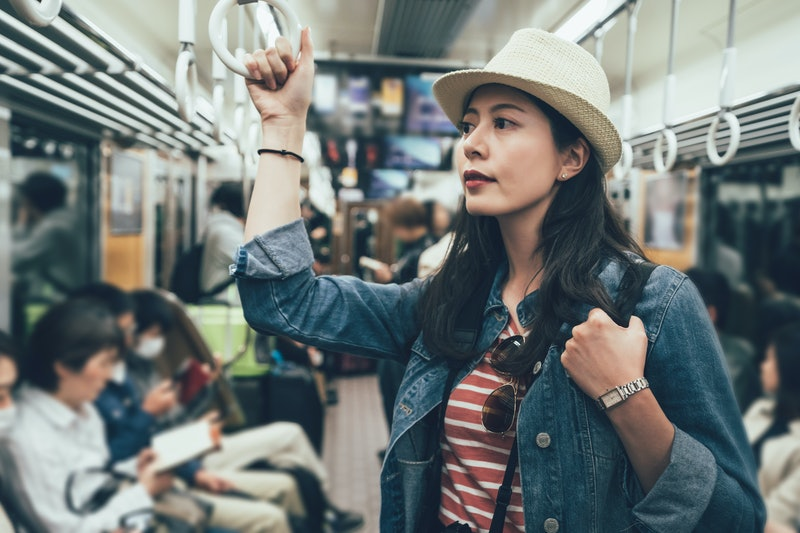 asian travel woman taking underground metro standing holding handle on train. female backpacker in subway by people sitting reading resting on seat. girl waiting for her destination arrived in japan.