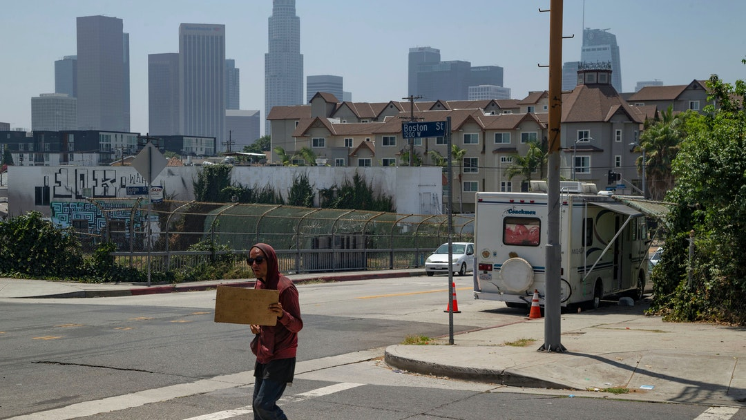 A homeless man pan handles next to a RV vehicle parked on an overpass of the CA-101 freeway in the Echo Park area of Los Angeles . Los Angeles has restored regulations barring people from sleeping at night in vehicles on residential streets or living anytime in vehicles within a block of parks, schools, preschools or daycare facilities. The City Council unanimously approved regulations Tuesday, July 30