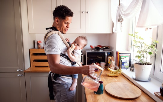 A father with small toddler son in carrier in kitchen indoors at home.