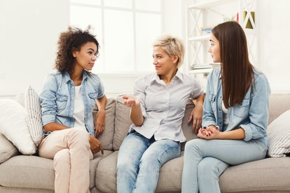 Happy female friends chatting at home. Three young women having friendly talk, gossiping and smiling, slumber party, copy space