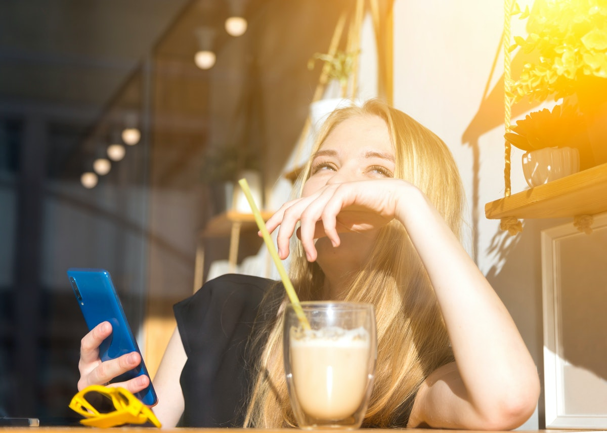 happy smiling young blond woman drinking a latte in a cafe for a glass, sunglasses and phone in the foreground. morning sun, bright summer day