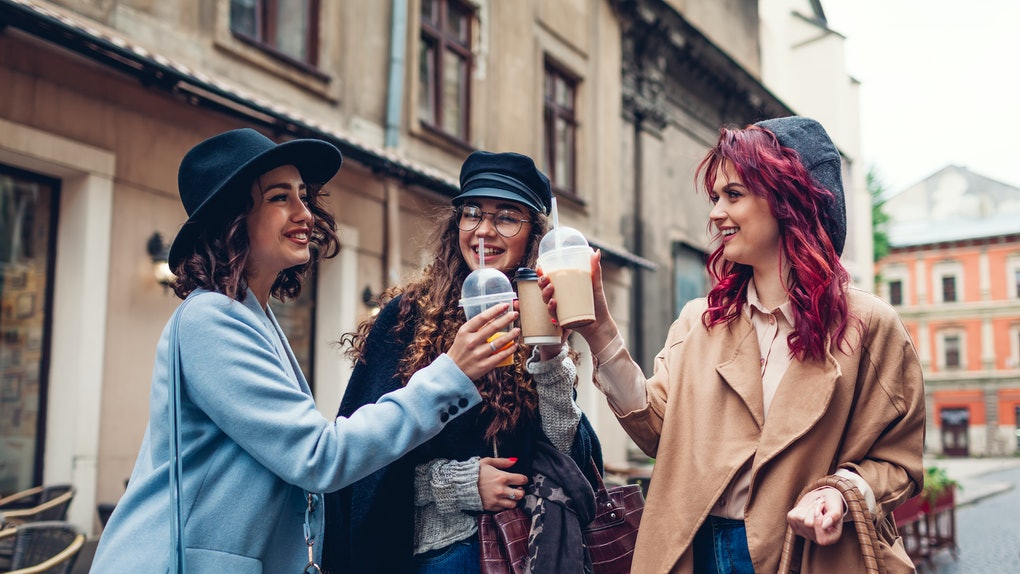 Three female friends having drinks outdoors. Women clinking coffee, orange juice and tea cups