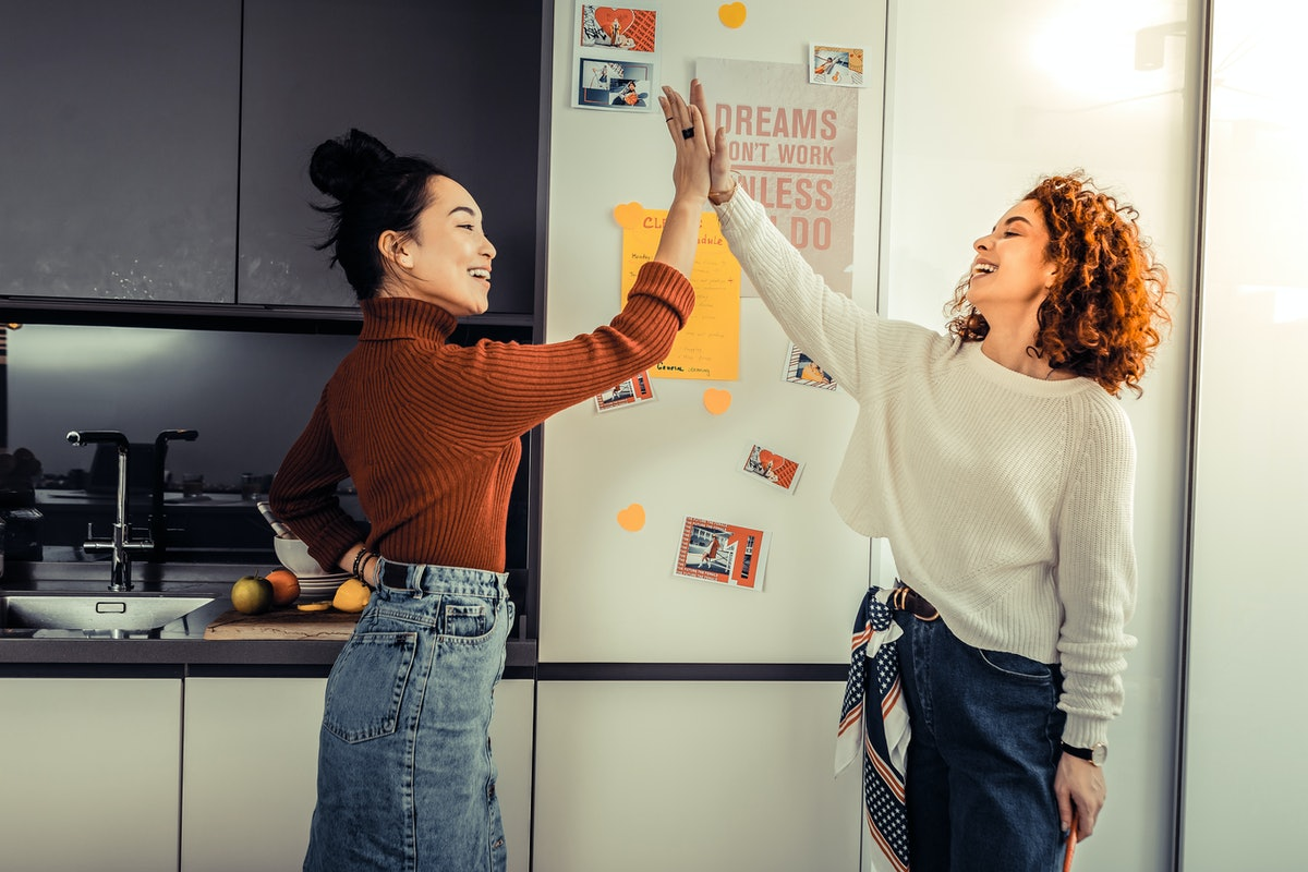 Giving high five. Two friends giving high five to each other after cleaning the apartment