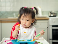 Toddler with pigtails eating peas and carrots at home.