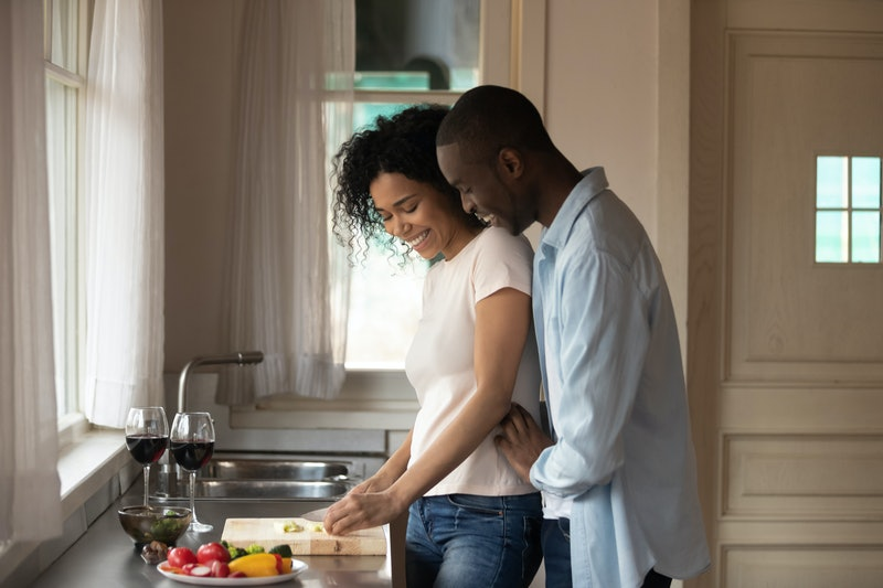 A happy, trendy couple embraces while chopping vegetables in their kitchen on a sunny day.