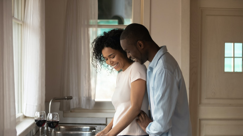 30s african couple talking stand in kitchen at modern home two glasses red wine on countertop, husband cuddle wife from behind, girl hold knife cut vegetables. Romantic dinner cooking together concept