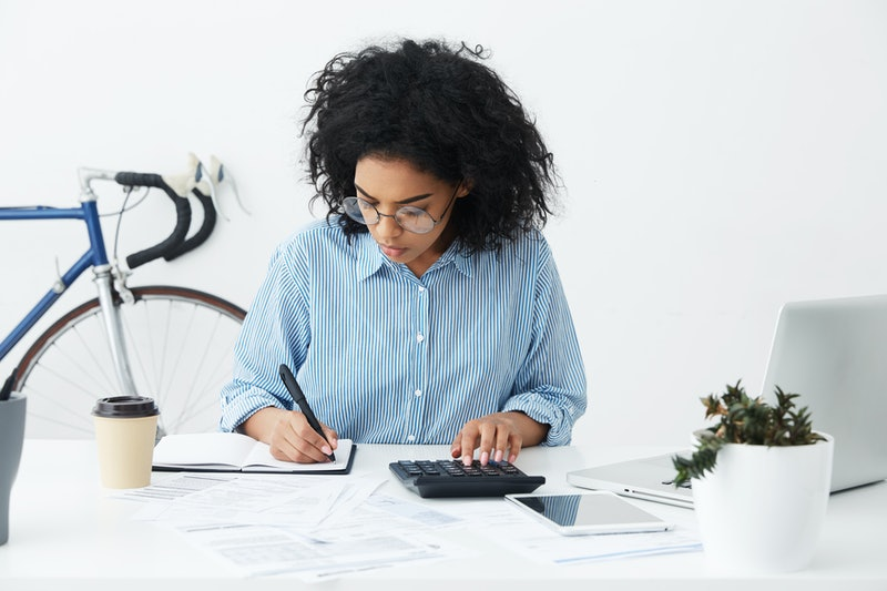 Portrait of attractive hardworking businesswoman with Afro hairstyle busy doing paperwork at office desk, working through finances, using calculator and making notes in her notebook with pen