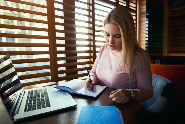 Portrait of smiling female with beautiful blond hair planning working schedule while sitting n modern coffee shop