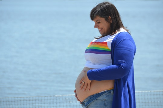 closeup portrait profile view of pregnant mom with white shirt with rainbow pulled up over her belly...