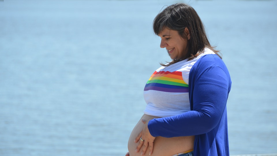 closeup portrait profile view of pregnant mom with white shirt with rainbow pulled up over her belly blue sweater hand on belly in front of blue water wearing jeans gay pregnancy rainbow baby
