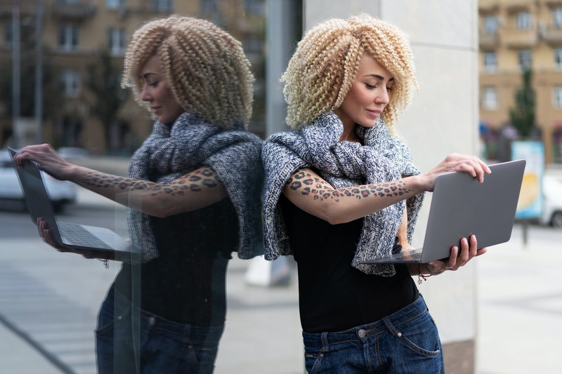european hipster girl with tattoo on her hand and afro hairstyle work on laptop on street, in fresh air. Freelance, creative freedom, creative. student learning