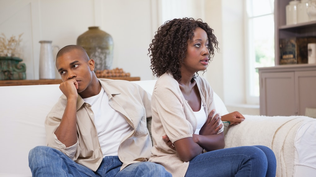Unhappy couple arguing on the couch at home in the living room