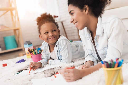 Mom and little girl lie on the floor with felt-tip pens. They draw on paper. They have fun together. Kindergarten teacher and kid concept.