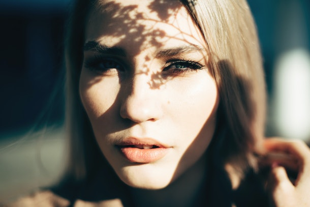 Closeup portrait of attractive blonde girl with shadows on the face.