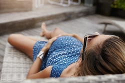 Pregnancy and motherhood concept. Young Caucasian pregnant woman in shades relaxing outdoors, having...