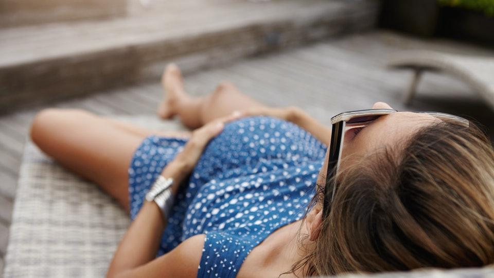 Pregnancy and motherhood concept. Young Caucasian pregnant woman in shades relaxing outdoors, having nap on sunlounger, holding hands on her tummy. Expectant mother in blue dress resting in open air