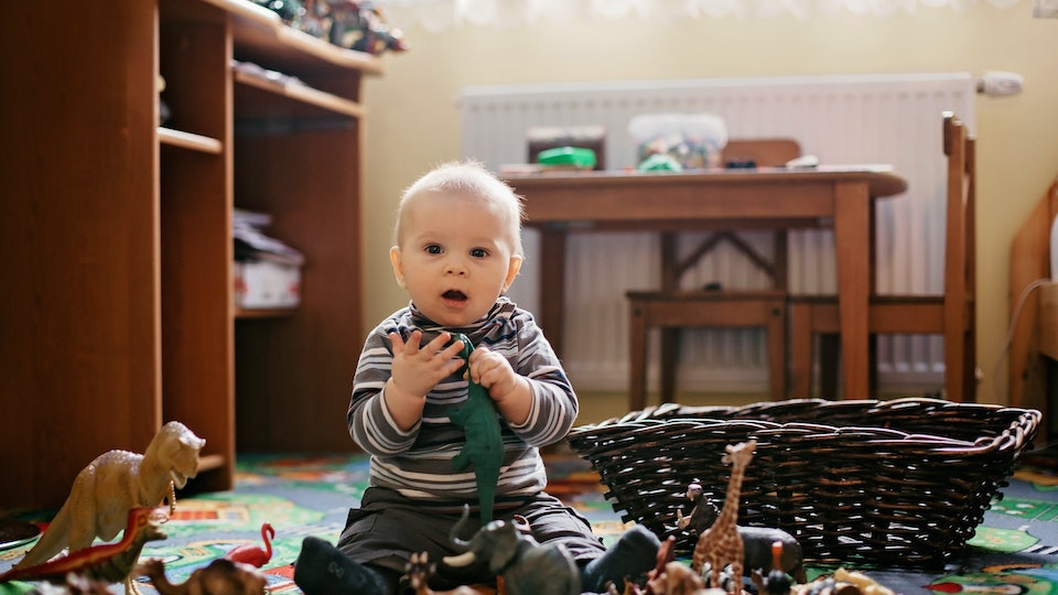 Beautiful little baby boy, toddler smiling at camera, animals and dinosaurs around him, indoor shot in kids playroom