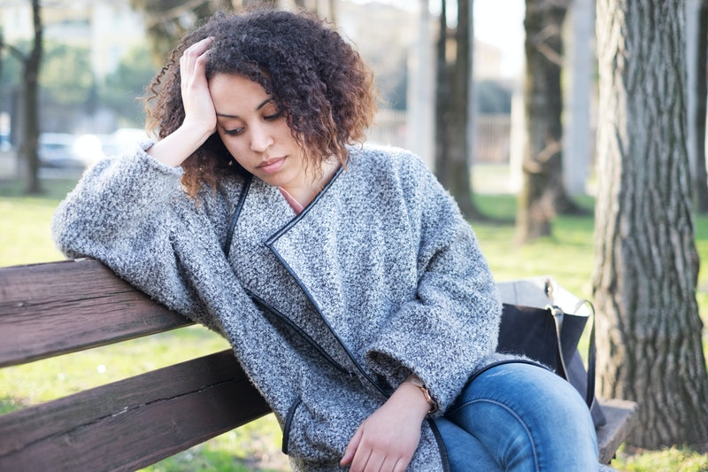 Sad black woman seated alone on a bench at the park