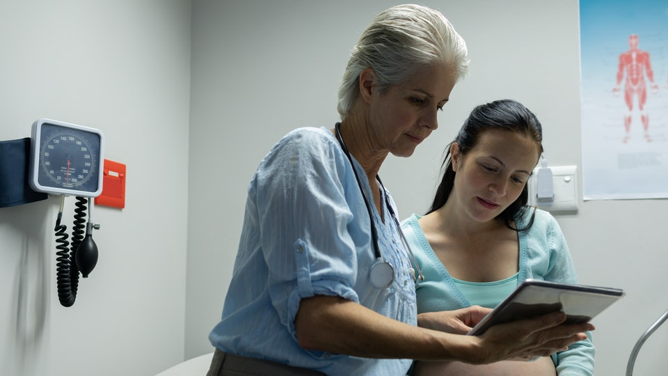 Front view of Caucasian female doctor discussing with pregnant woman over digital tablet in examination room at hospital