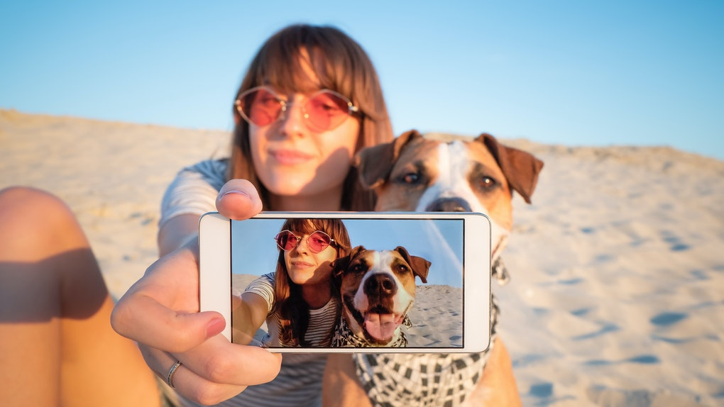 Human taking a selfie with dog. Best friends concept: young female makes self portrait with her puppy outdoors on a beach