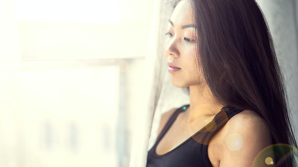 A young Korean girl looks out the window. Beautiful woman enjoys the morning. Wake up early in the morning and meet the dawn. Start life anew. Look into the future.