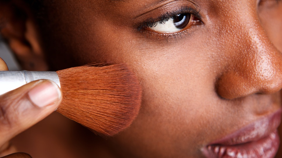 Close up side portrait of beautiful woman applying makeup with brush for smooth matte finish