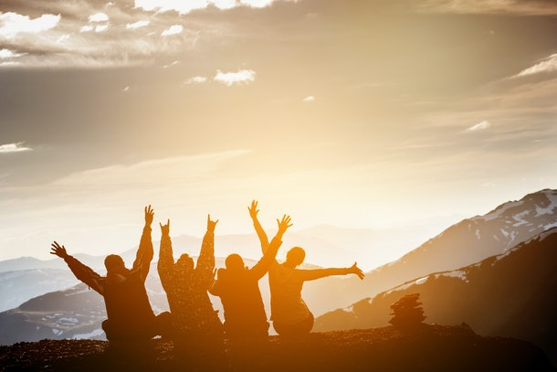 Group of friends sits on the top of mountain and having fun on mountains backdrop