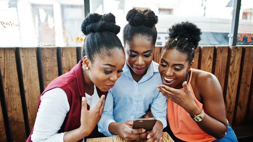 Three african american girls sitting on the table of caffe and looking on mobile phone.