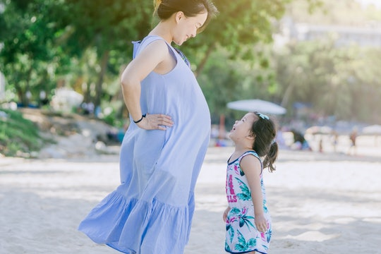 Photo of Happy family.Pregnant mother and daughter smiling relaxing and playing on the beach,Happy p...