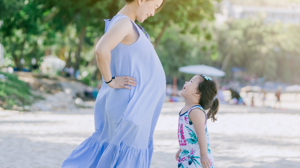 Photo of Happy family.Pregnant mother and daughter smiling relaxing and playing on the beach,Happy pregnant woman, little child daughter smiling tummy mother in summer day on the tropical beach.