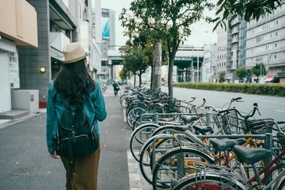 Back rear view of hipster girl walking on city street in osaka japan. young female backpacker in hat go through bikes in parking lot for bicycles in modern urban walkway with shop close on side.