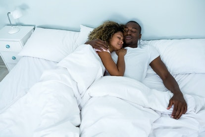 Young couple sleeping together on bed in bedroom