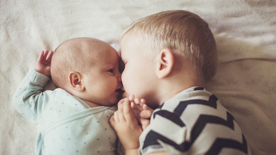 older brother kisses younger brother