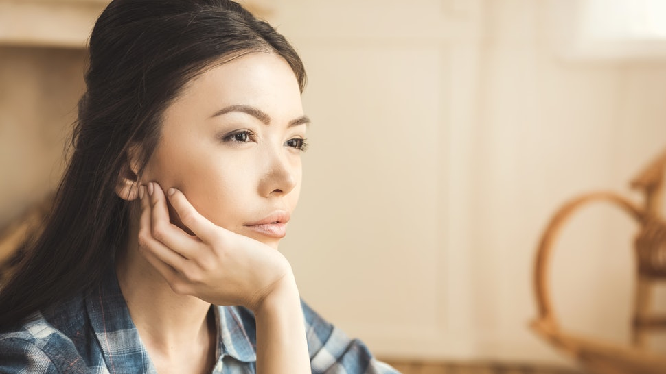 Portrait of young engrossed woman daydreaming with hand on chin