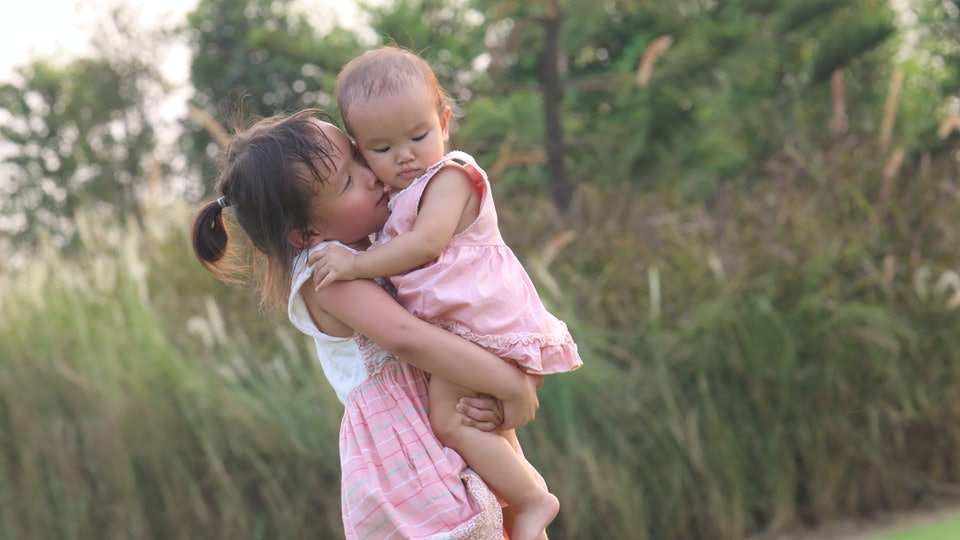 Two sisters are in the park with cute pink dress. They're love each other so much. The big sister is kissing the toddler one.