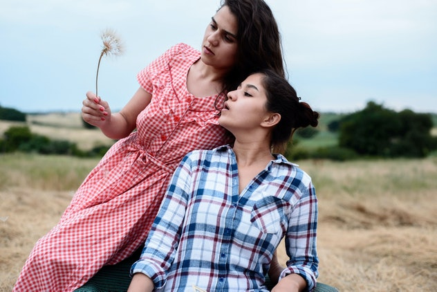 two sisters, in a plaid shirt, in a rustic style, sit on a chair, inflating the petals of a dandelion. World sister day