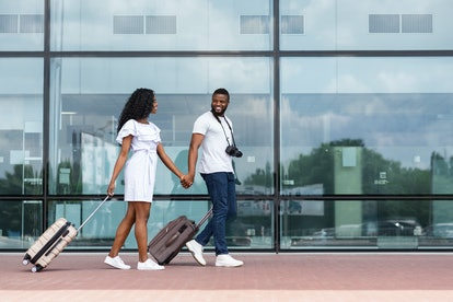 Going to travel. African couple walking with luggage near airport building, empty space