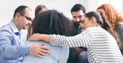 Support group meeting. Addicted people comforting upset woman at therapy session, free space