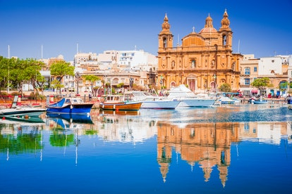 Valletta, Malta. Msida Marina boat and church reflection into water.
