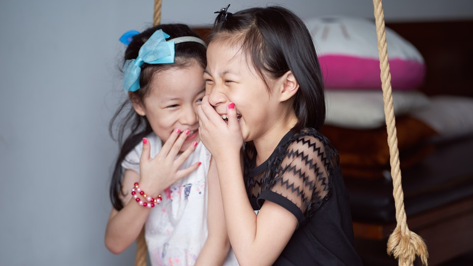 Asian sisters laughed happily sit on inhouse swing set