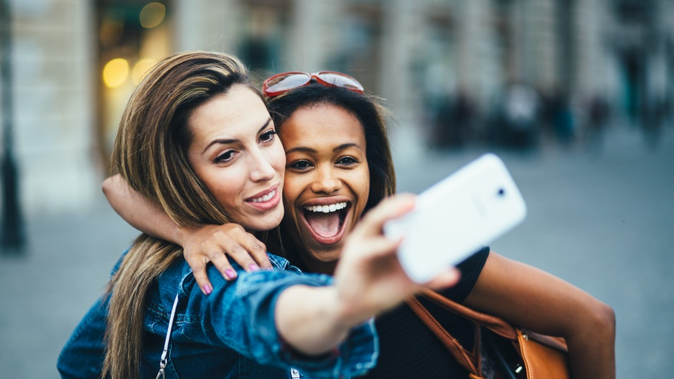 Multi ethnic Friends having fun in city taking selfie