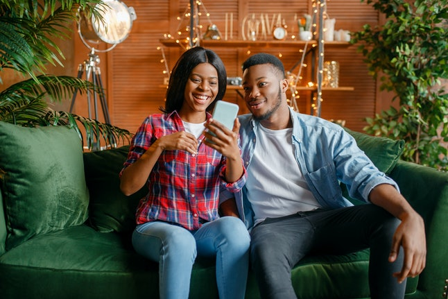 Black couple sitting on sofa and looking on phone