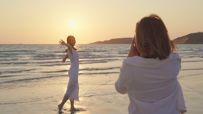 Young Asian lesbian couple using camera taking photo each other near beach. Beautiful women lgbt couple happy romantic moment when sunset in evening. Lifestyle lesbian couple travel on beach concept.